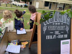 Kinderen uit het Lepelkruidhof vullen een ideeënformulier in over het opknappen van de Kruidenbuurt