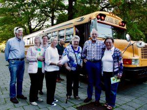 Foto van bewoners voor de gele schoolbus